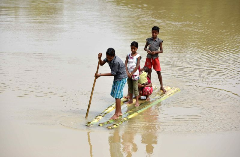 A man rows a raft in flood hit Jamunamukh village in Assam's Hojai district on June 18 , 2018.(Image Source: IANS)