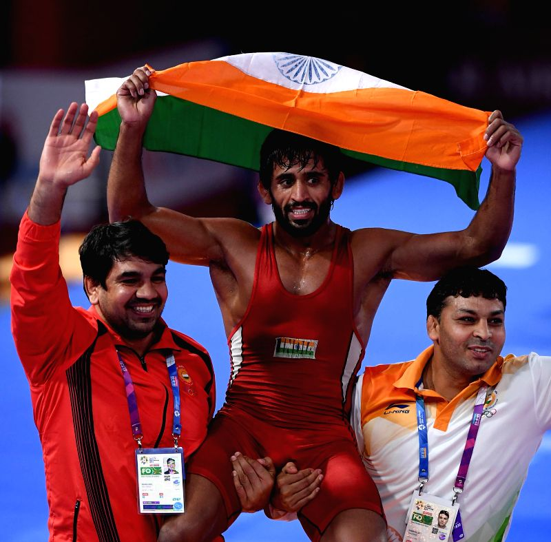 : Bajrang Punia (C) of India celebrates after winning gold medal of Men's Wrestling Freestyle 65 kg Final against Takatani Daichi of Japan in the 18th Asian ...(Image Source: IANS)