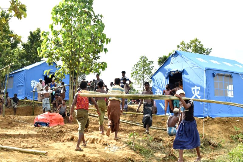 DHAKA, Oct. 4, 2017 - People walk near Chinese relief tents at a camp in Cox's Bazaar district, Bangladesh, on Oct. 3, 2017. China has sent relief supplies for Rohingya refugees in Bangladesh ...