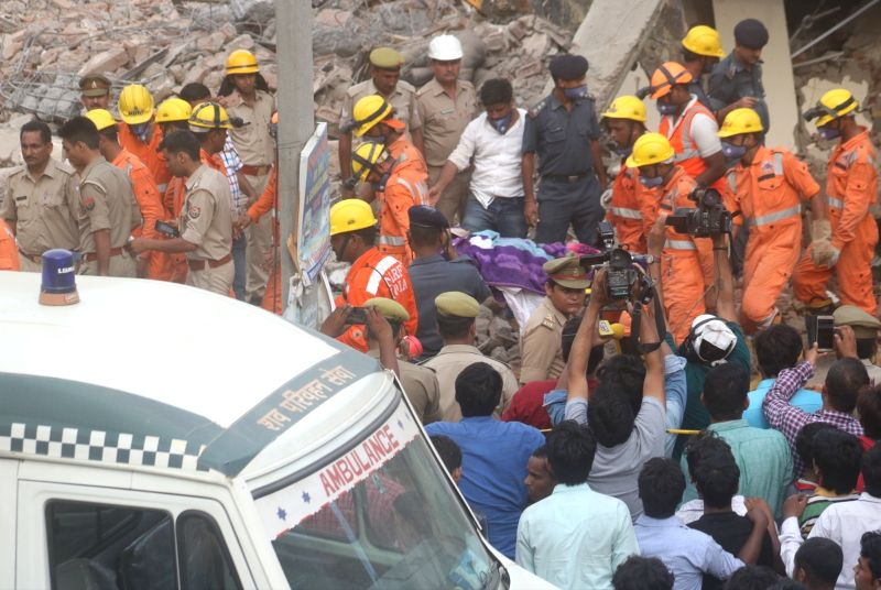 Greater Noida: Rescue personnel recover the body of one of the persons killed in Greater Noida twin-building collapse on July 18, 2018. At least 50 people were believed trapped under the concrete ...(Image Source: Bidesh Manna/IANS)