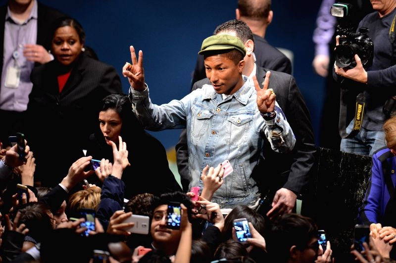 Singer Pharrell Williams poses to fans during an event marking the International Day of Happiness at the UN headquarters in New York, on March 20, 2015. ...