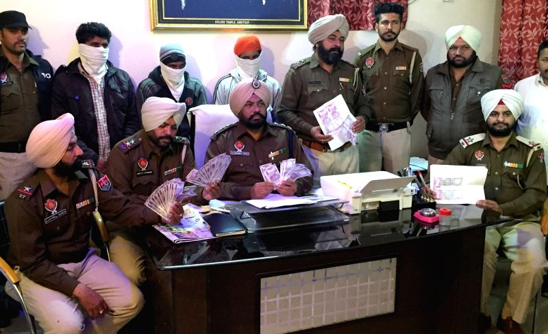 Police present before press three persons held for printing fake notes Rs 2000 denomination in Amritsar, on Dec 20, 2016.