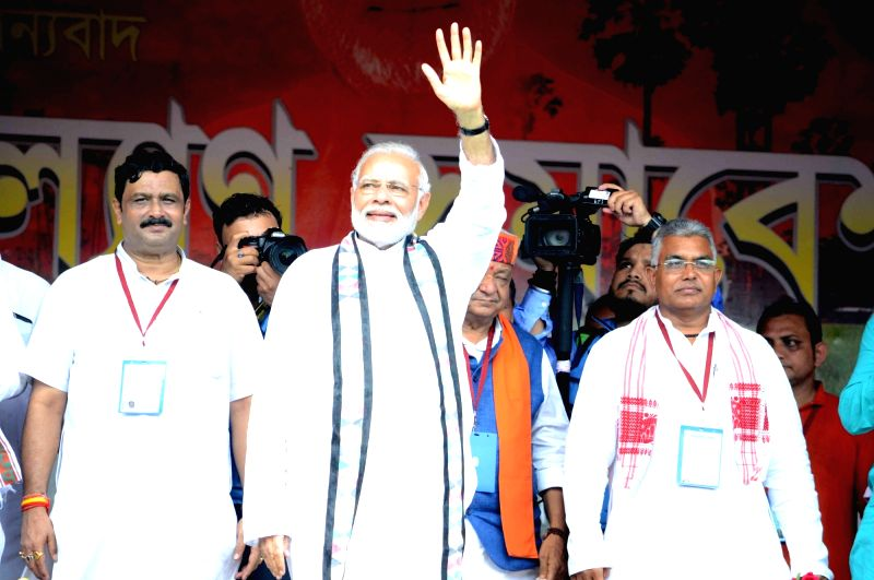 "Prime Minister Narendra Modi waves at farmers during ""Kisan Kalyan"" rally, in West Bengal's Midnapore on July 16, 2018. Also seen BJP leaders Rahul Sinha and Dilip Ghosh.(Image Source: IANS)"